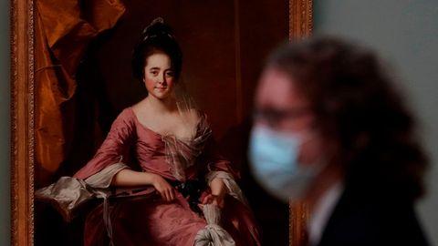 Eine Besucherin mit Maske steht vor einem Gemälde im Metropolitan Museum of Art