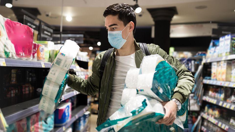 Ein junger Mann kauft in einem Supermarkt Toilettenpapier