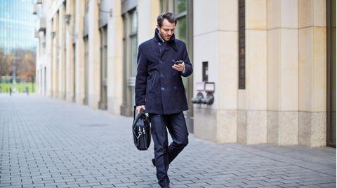 Mann schaut im Gehen aufs Handy