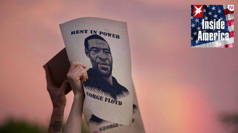 Demonstranten in Minneapolis halten während einer Protestaktion Plakate mit dem Porträt von George Floyd in die Höhe.