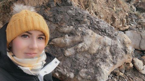 Die Archäologin Marie Woods mit dem Dinosaurier-Fußbadruck im Hintergrund