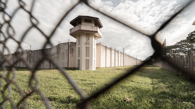 Blick auf Gefängnisturm durch Maschendrahtzaun
