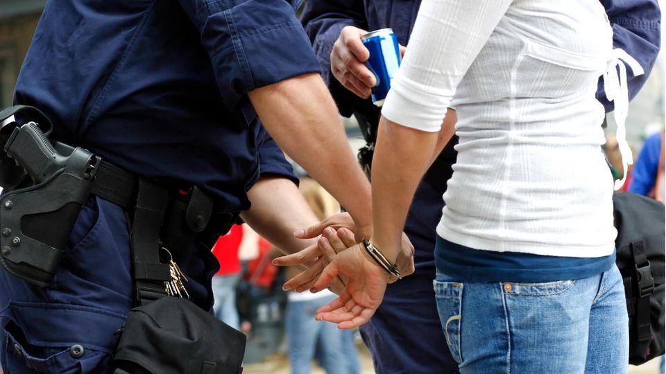 Frau wird von Polizisten verhaftet