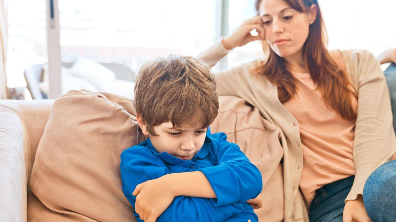 Junge sitzt neben seiner Mutter auf dem Sofa