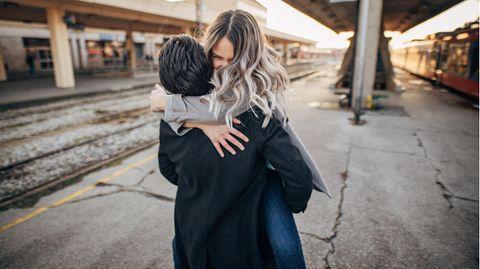 Mann nimmt Frau am Bahngleis in die Arme