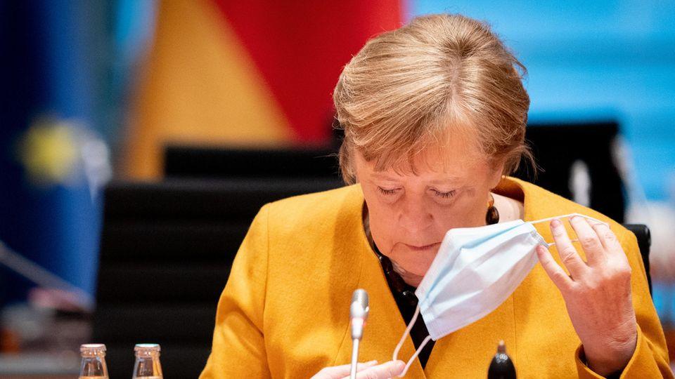In einem gelben Blazer sitzt Bundeskanzlerin Angela Merkel an einem Tisch mit silbernem Mikro und hantiert mit einer OP-Maske