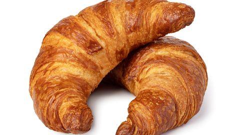 Auf einem weißen Untergrund liegen zwei Croissants. Eines liegt mit einer Spitze auf dem anderen