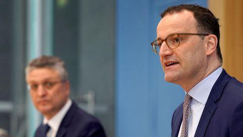 Zwei Männer mit Brillen und Anzügen sitzen auf dem Podium der Bundespressekonferenz vor einer hellblauen Wand
