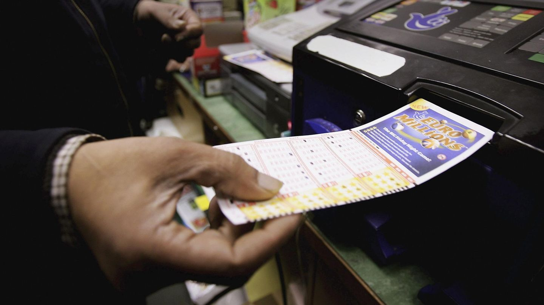 Ein Kunde führt seinen Lottoschein in ein Lesegerät