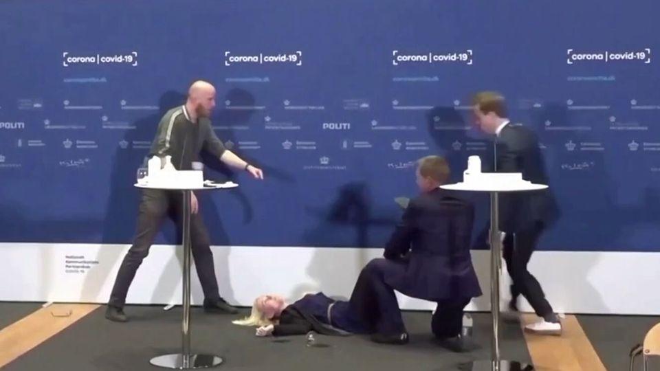 Mehrere Männer kümmern sich um die bei einer Coronavirus-Pressekonferenz in Dänemark zusammengebrochene Beamtin