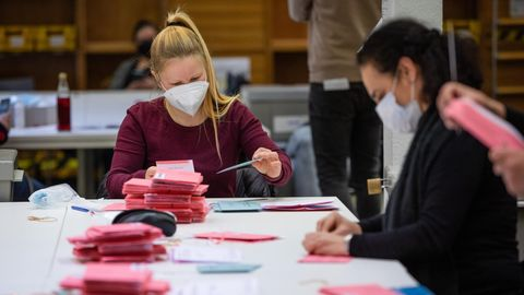 Wahlhelferinnen und Wahlhelfer kontrollieren Stimmzettel.