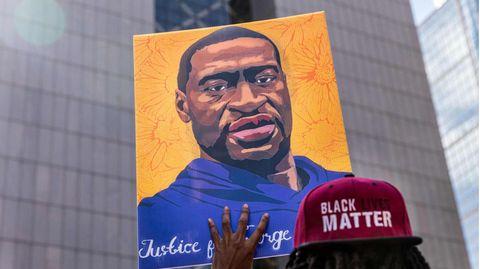 Ein Demonstrant hält ein Bild des verstorbenen George Floyd in die Höhe
