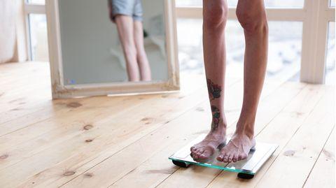 Eine dünne Frau steht auf einer Waage. Ihre Beine und Knie sind sehr dünn
