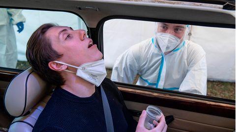 Ein junger Mann sitzt im Auto und legt gurgelnd seinen Kopf zurück, während ein Mann in Schutzkleidung von außen beobachtet
