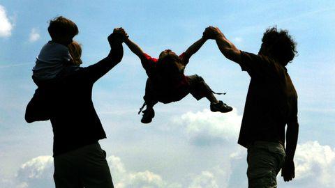 Im Gegenlicht sind die Konturen zweier Erwachsener zu sehen, die eine Kind an den Armen zwischen sich schaukeln