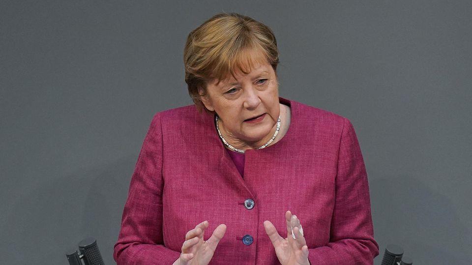 Bundeskanzlerin Merkl steht im dunkelpinken Blazer am Rednerpult im Bundestag und gestikuliert mit beiden Händen auf Brusthöhe