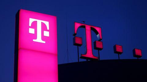 Das Logo der Deutschen Telekom leuchtet vor einem dunklen Himmel auf dem Dach der Unternehmenszentrale