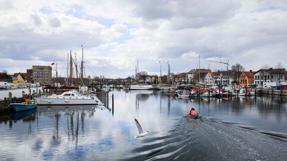 Zwei Angler fahren auf einem Bott durch den Hafen von Eckernförde.