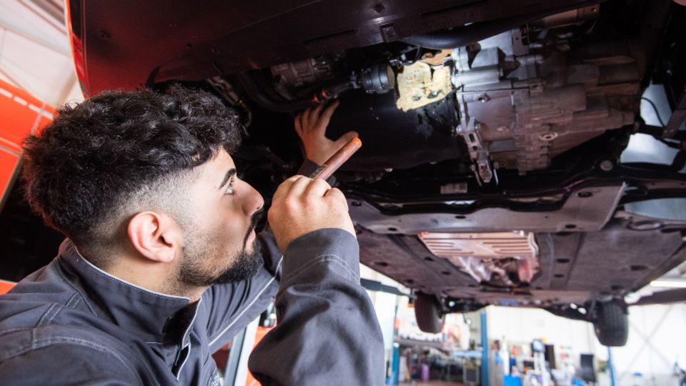 KfZ-Mechatroniker untersucht Schäden an Unterseite eines Wagens.