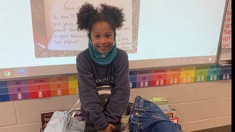 Die 7-jährige Kamryn lächelt in die Kamera, während um sie herum Hosen liegen
