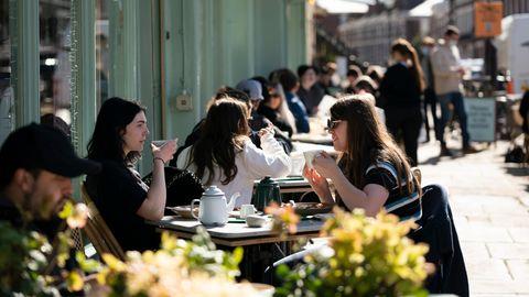 Großbritannien, Liverpool: Besucherinnen sitzen an Tischen auf der Terrasse eines Restaurants