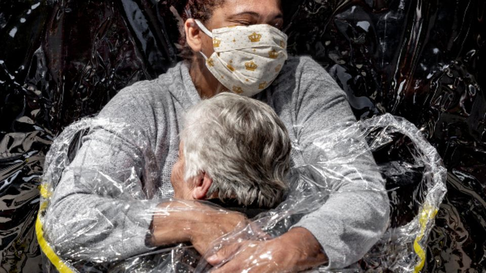 Die erste Umarmung seit fünf Monaten durch einen Plastikvorhang