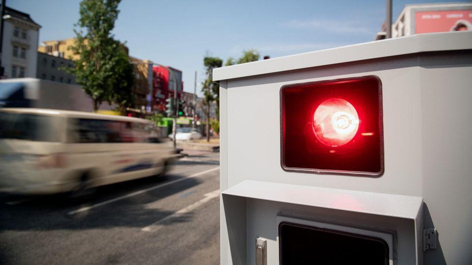 Ein Blitzer löst aus, während im Hintergrund ein Taxi mit Bewegungsunschärfe vorbeifährt