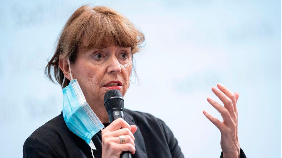 Eine ältere Dame mit rotbraunen Haaren hat eine OP-Maske am rechten Ohr hängen und spricht in ein Mikrofon