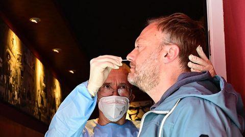 Ein Mann in medizinischer Schutzkleidung steht in der Tür einer Bar und steckt einem anderen Mann ein Wattestäbchen in die Nase