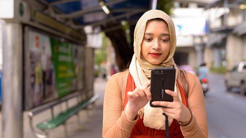 Eine Muslima trägt ein Kopftuch und blickt auf ihr Handy