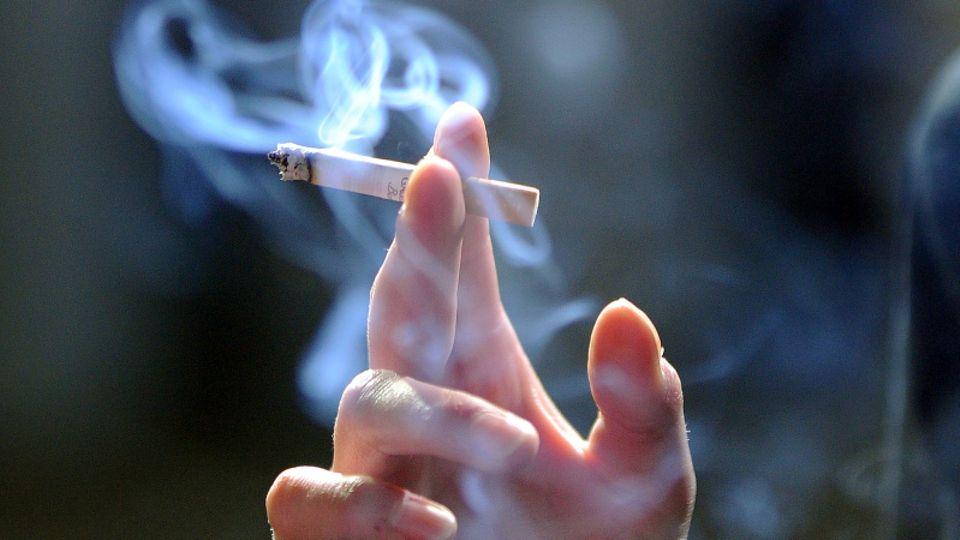 Eine Hand hält eine angezündete Zigarette