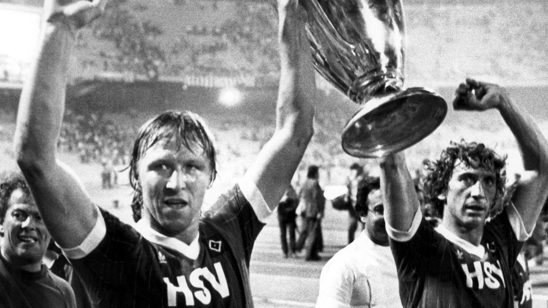 Horst Hrubesch hält mitDitmar Jakobs (re.) den Landesmeisterpokal in die Luft
