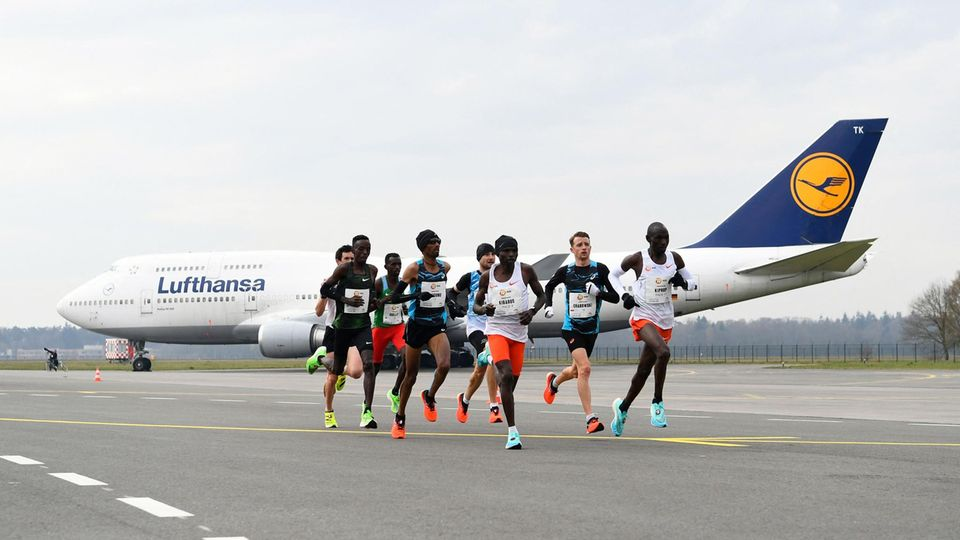 Enschede, Niederlande. Eine Gruppe Marathon-Läufer rennt an einer Lufthansa-Maschine vorbei. Der Enschede Airport Twente istErsatzaustragungsort für den abgesagten Elite-Marathon in Hamburg. DerElite-Lauf findet auf einem eigens dafür angelegten Kurs ohne Zuschauer statt.Mehr als 70 Athleten werden nun dort versuchen, sich einen Platz für die Olympischen Spiele in Tokio zu sichern.Der Mission Marathon war zunächst für den 11. April in Hamburg geplant, doch die aktuelle Corona-Situation zwang die Veranstalter zu einer Absage.