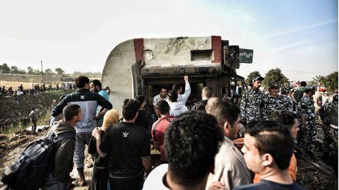 Männer und Soldaten der Streitkräfte Ägyptens stehen neben einem umgekippten Waggon eines Zugs
