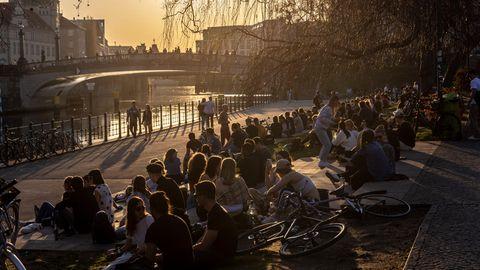 Coronavirus-Aerosole im Freien: Menschen sitzen in einem Park in Berlin zusammen
