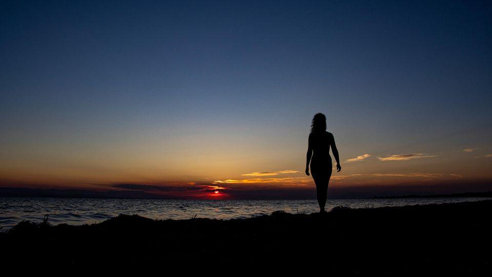 Eine Frau steht bei Sonnenuntergang am Strand