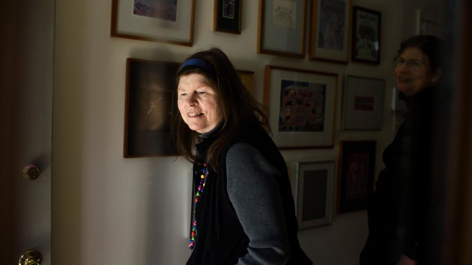 Lonni Sue vor einer Wand mit ihren Gemälden