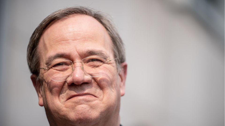 Ein älterer weißer Mann mit randloser Brille und dunkelgrauem Seitenscheitel lächelt, während ihm die Sonne ins Gesicht scheint