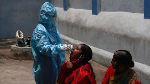 In der indischen Stadt Hyderabad nimmt ein Mitarbeiter des Gesundheitswesens einer Frau einen Mundabstrich ab