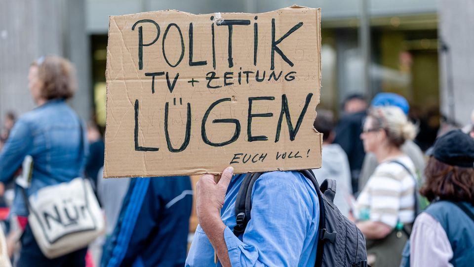 Ein Mann hält ein Plakat während einer Demonstration in Hamburg gegen die Corona-Maßnahmen