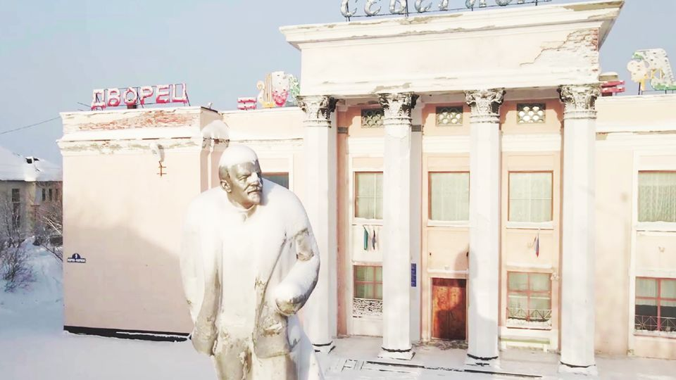 Von Schnee bedeckte Statue in einer verlassenen russischen Stadt