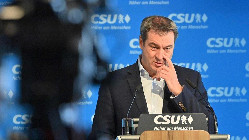 Kamera ist gerichtet auf CSU-Chef Markus Söder - Er fasst sich am Rednerpult an die Nase