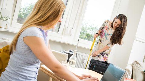 Während eine Frau am Schreibtisch am Laptop arbeitet, wischt eine andere den Boden