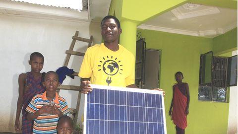Eine Familie aus der Nähe von Arusha nimmt ihre neue Solaranlage in Empfang