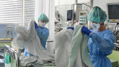 Zwei Intensivschwestern bereiten ein Bett für Patienten vor.