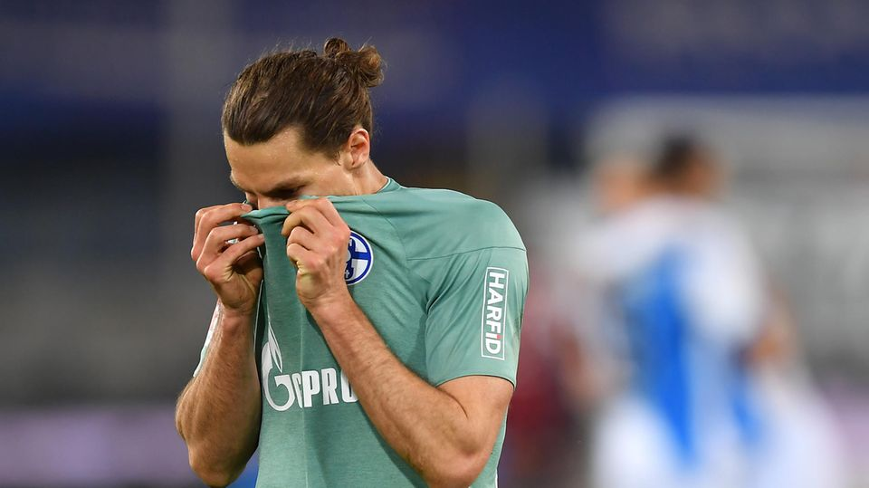 A footballer with brown braid hides his face in the copper-green Schalke jersey