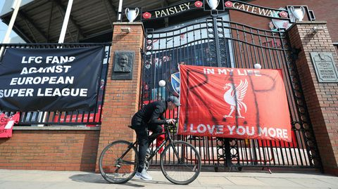 Zur Super League: Ein Mann fährt mit dem Fahrrad an einem Banner vor dem Anfield Stadion in Liverpool vorbei.
