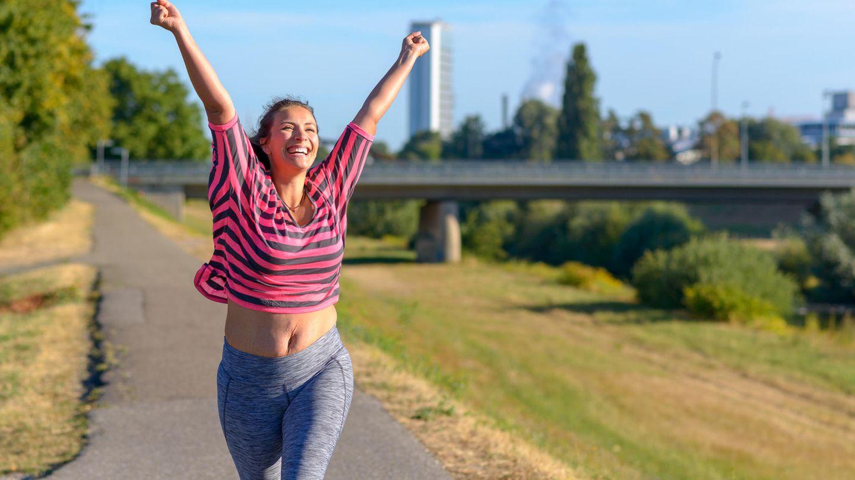 Eine Frau joggt an einem Sommertag und freut sich über ihren Trainingserfolg