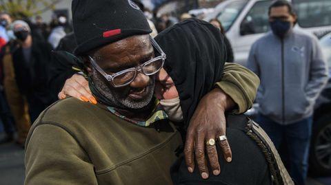 Ein schwarzer Mann mit grauem Bart und schwarzer Mütze und eine Frau mit Kapuze und Mundschutz liegen sich in den Armen