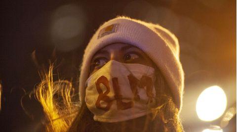 """Eine Frau mit rosa Wollmütze trägt im Licht einer Straßenlaterne einen Mundschutz mit aufgemaltem """"BLM"""""""